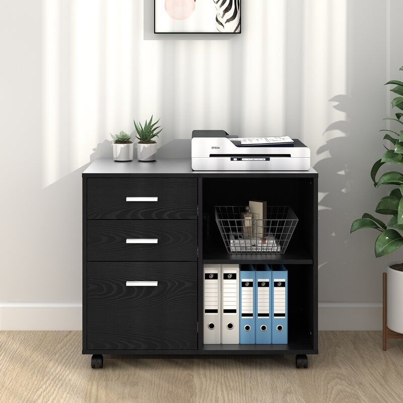 A black filing cabinet with 2 shelves and 3 drawers filled with files and a printer and plant decor on top