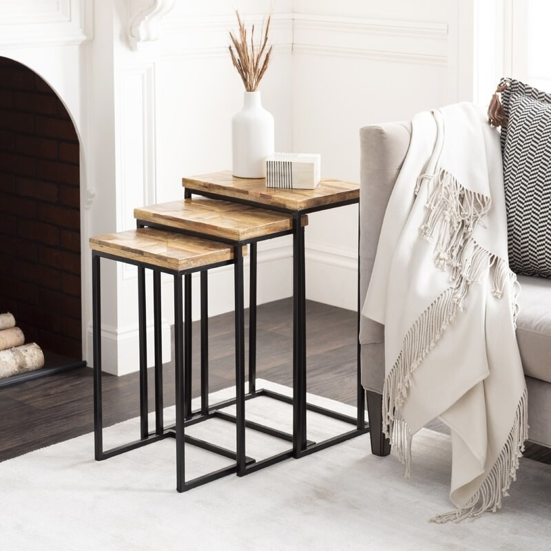 A set of 3 nesting tables with a brown wooden tops and black metal bases displayed next to a couch