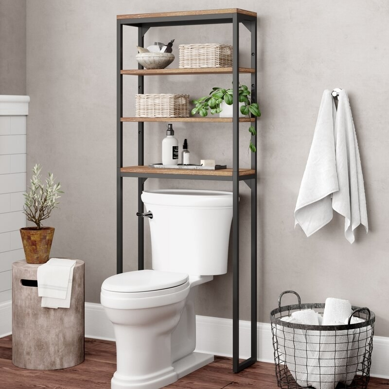 An over-the-toilet shelving unit with 4 shelves that can hold items such as towels, toiletries, soaps, candles, frames, and much more