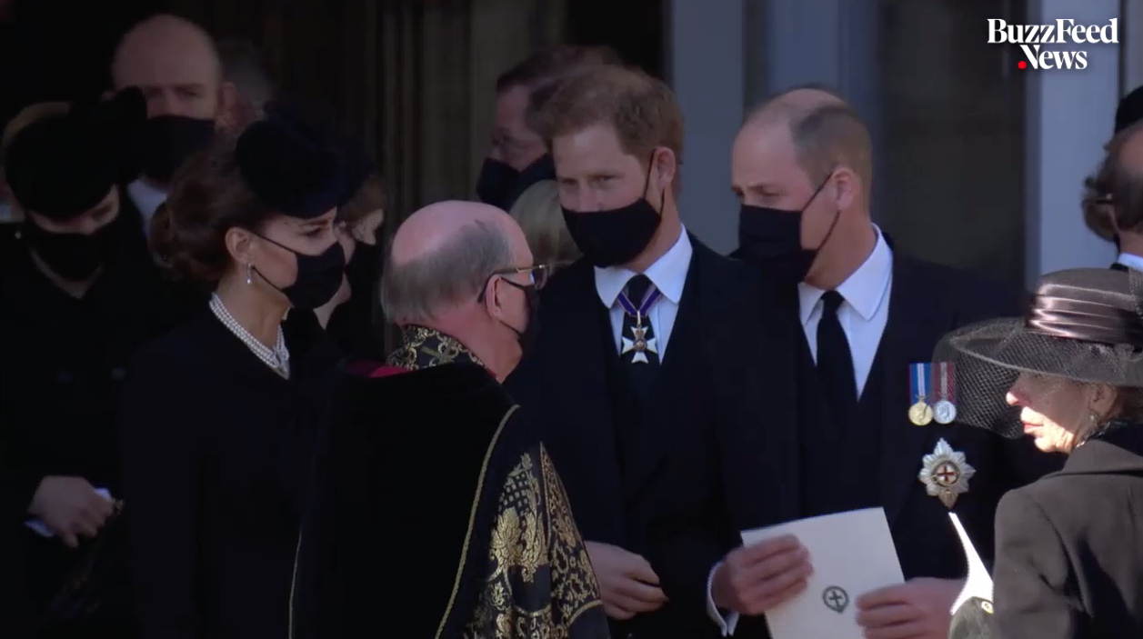 Catherine, Duchess of Cambridge, Prince Harry, and Prince William stand together, wearing masks