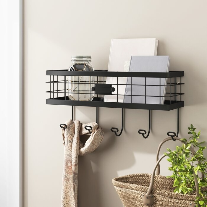 A black coat rack with 5 hooks and a basket mounted to the wall in an entryway