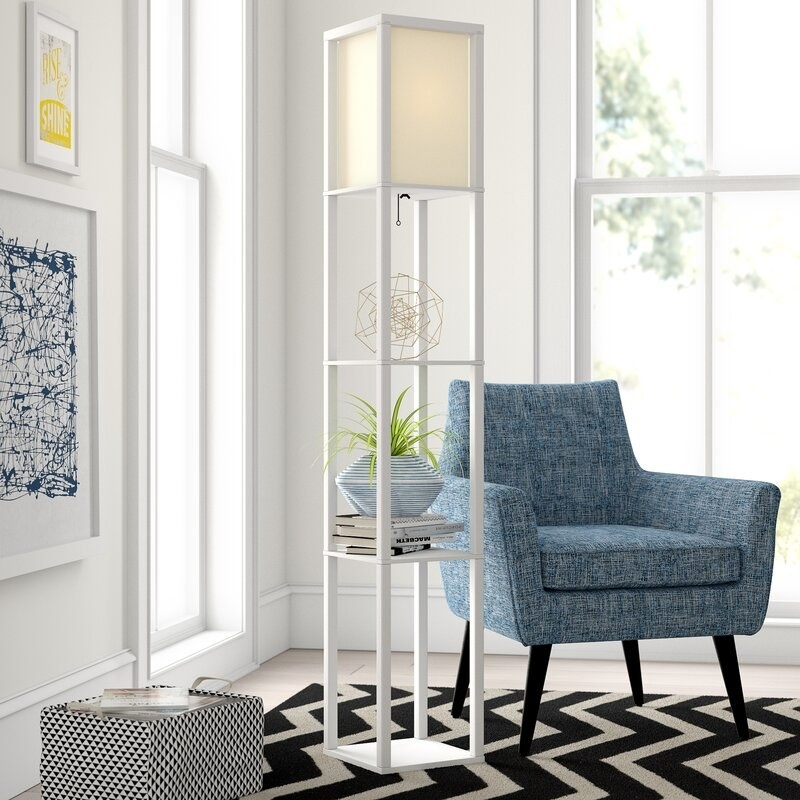A white floor lamp with 3 shelves displayed next to an accent chair