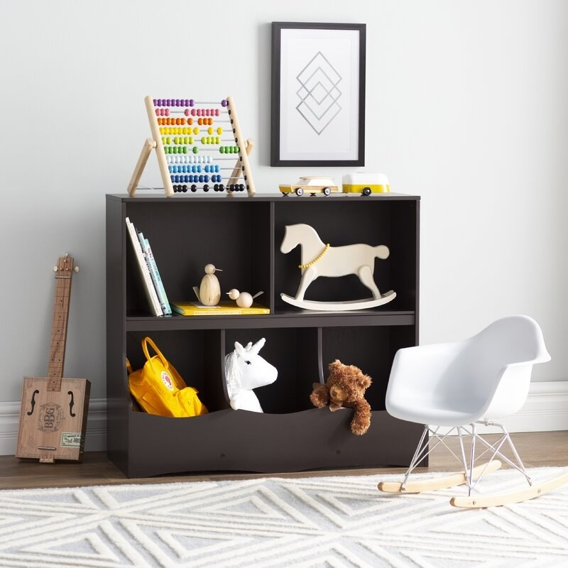 A wooden toy organizer with 3 cubbies and two shelves to hold toys, stuffed animals, and books