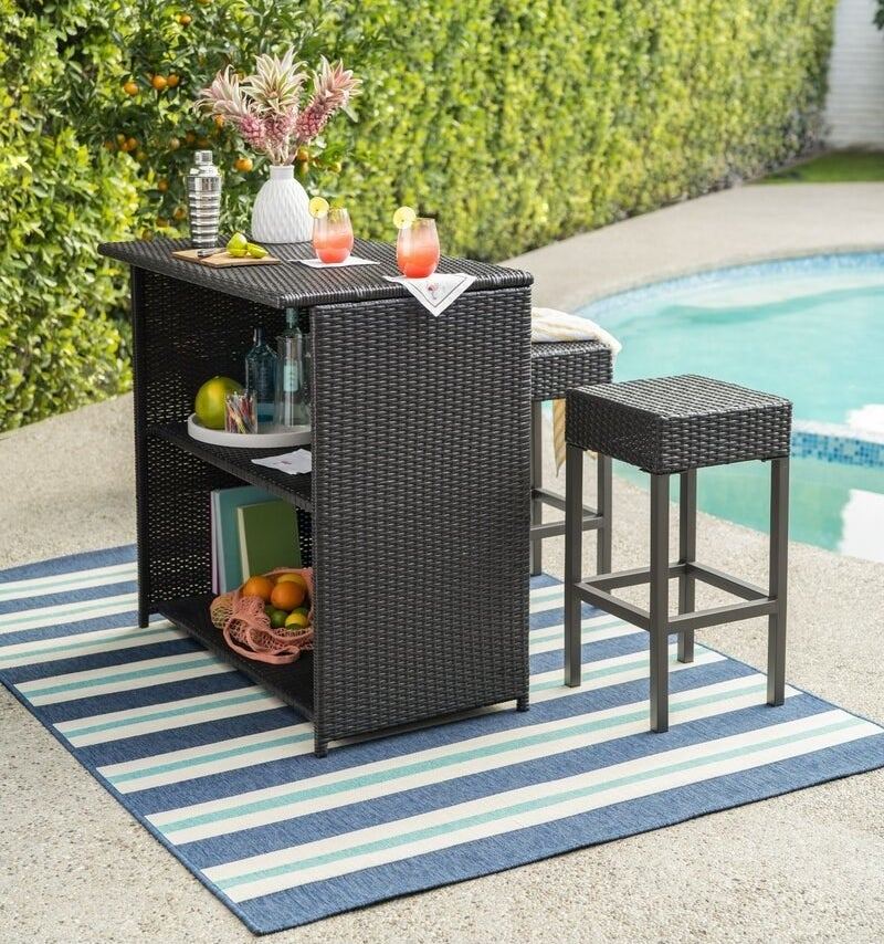 A wicker outdoor bar with two shelves and two stools displayed next to a pool