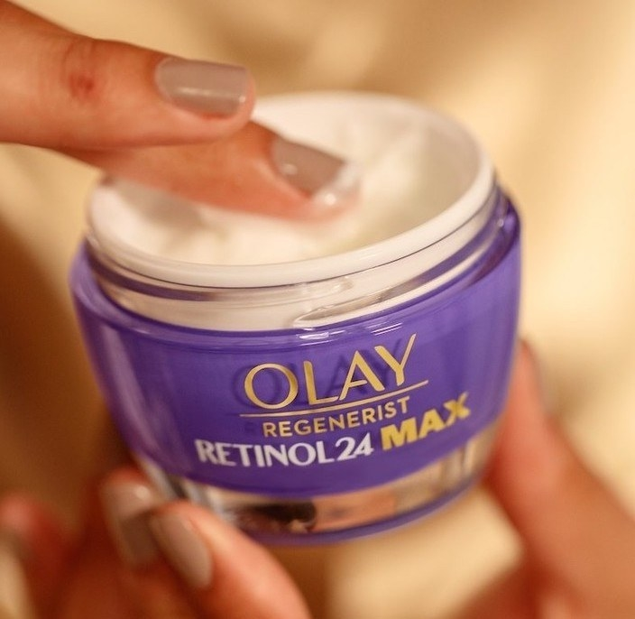 Fingers dipping into Olay retinol cream