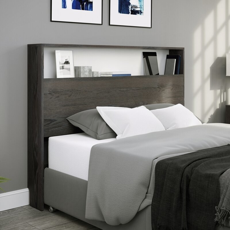 A charcoal colored wooden bookcase headboard with a shelf that can fit items such as your remote, books, glasses, and more