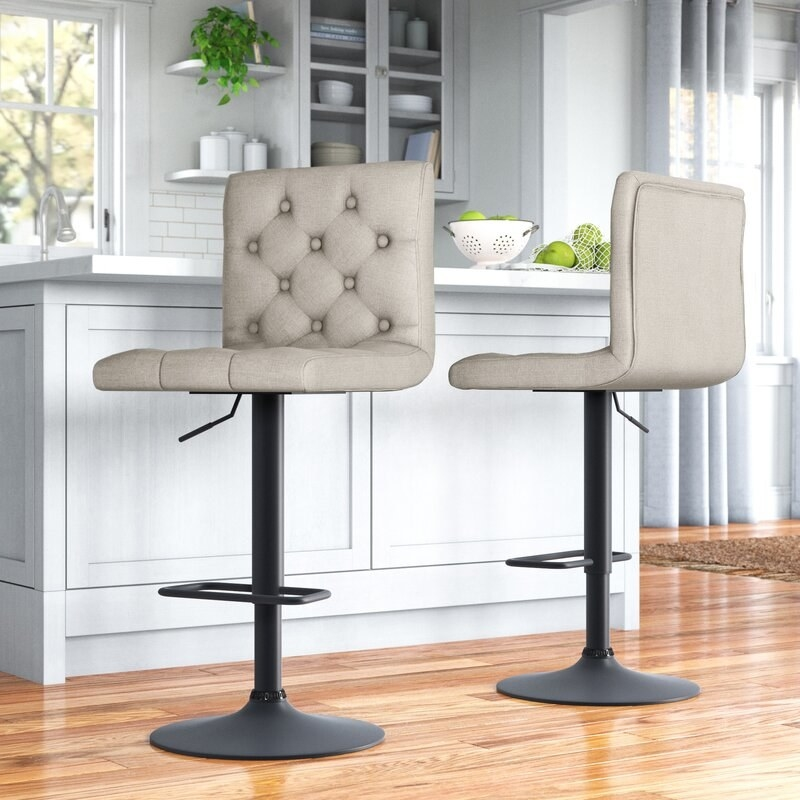 A set of two beige upholstered adjustable bar stools with a swivel feature displayed in front of a kitchen island