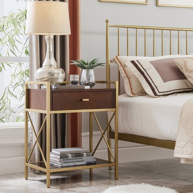 A walnut and gold metal nightstand that includes one drawer and and extra shelf at the base displayed in a bedroom