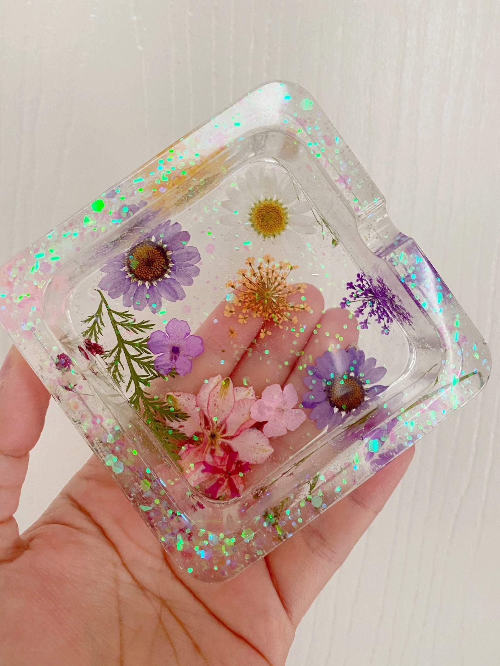 hand holding a square clear ashtray with iridescent glitter flecks and dried flowers inside