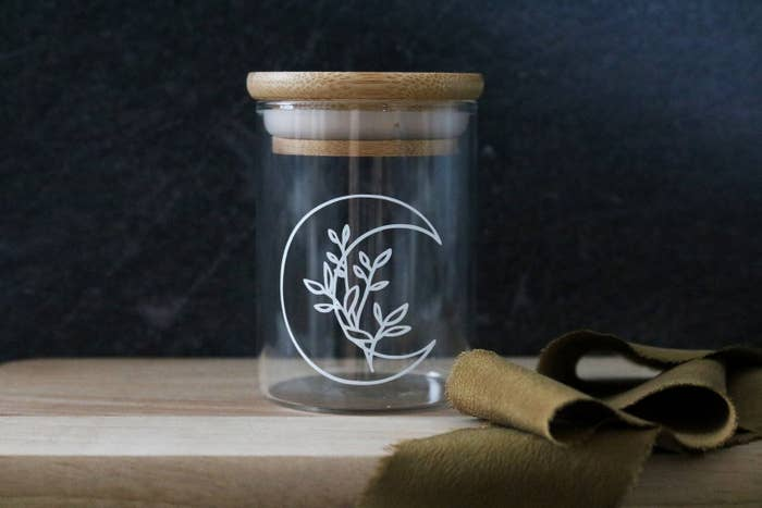 a small clear glass jar with a crescent moon animation on the front with flower sitting inside the crescent and a bamboo top