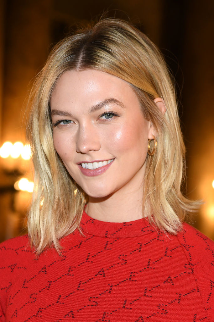 Karlie smiling and wearing a red top