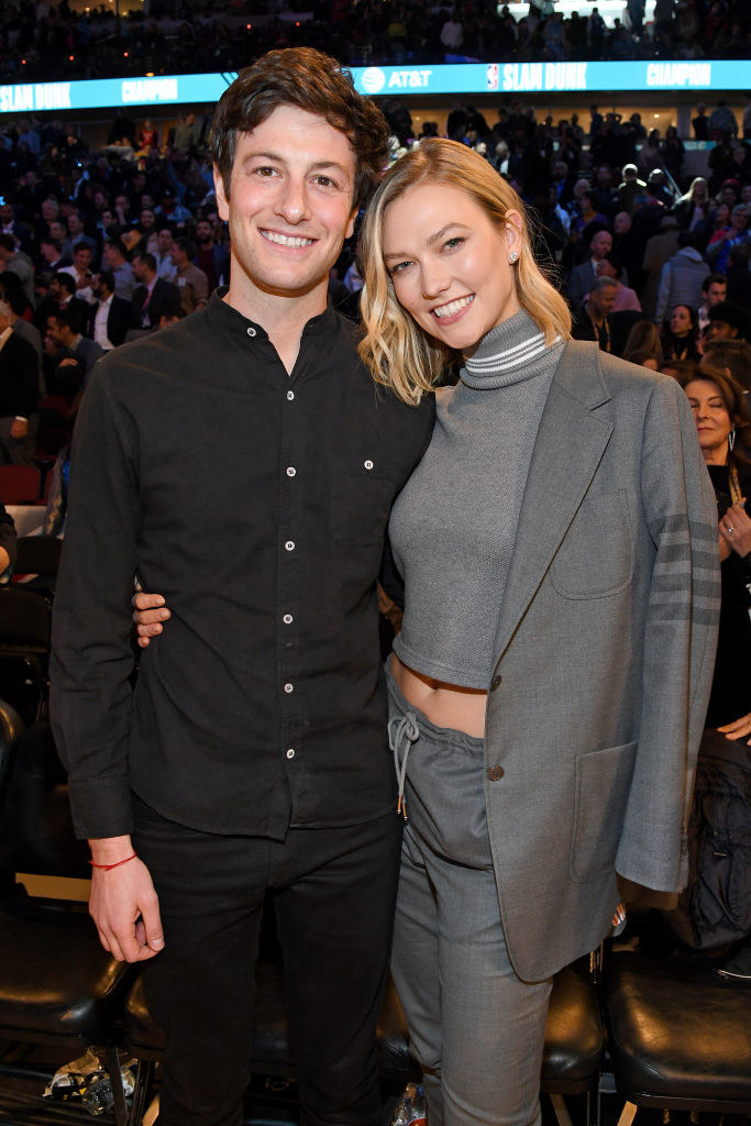 Josh and Karlie standing together with Karlie's arm around his waist