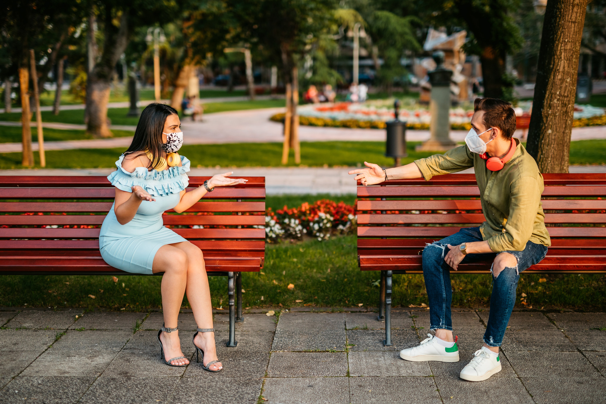 Two people sitting socially distanced on two benches and talking