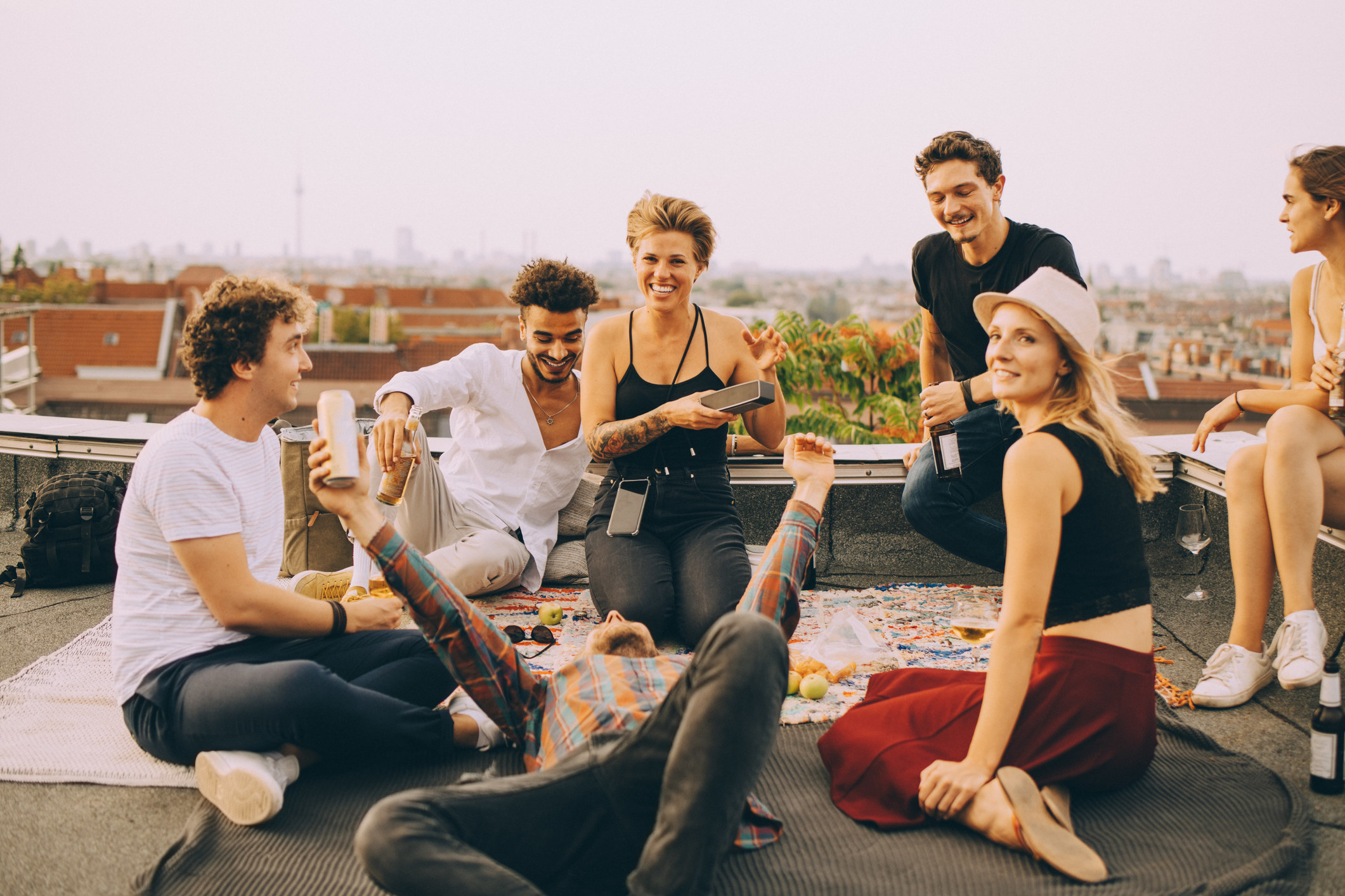 A group of people drinking and talking a rooftop