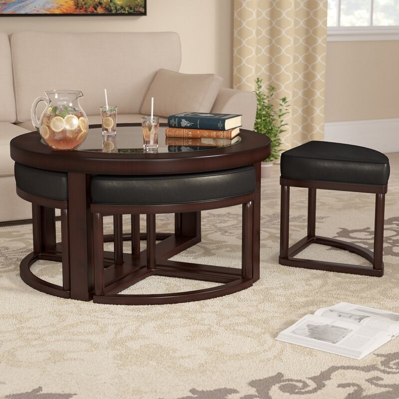 A brown coffee table with 4 nested stools that have black, faux leather upholstered cushions