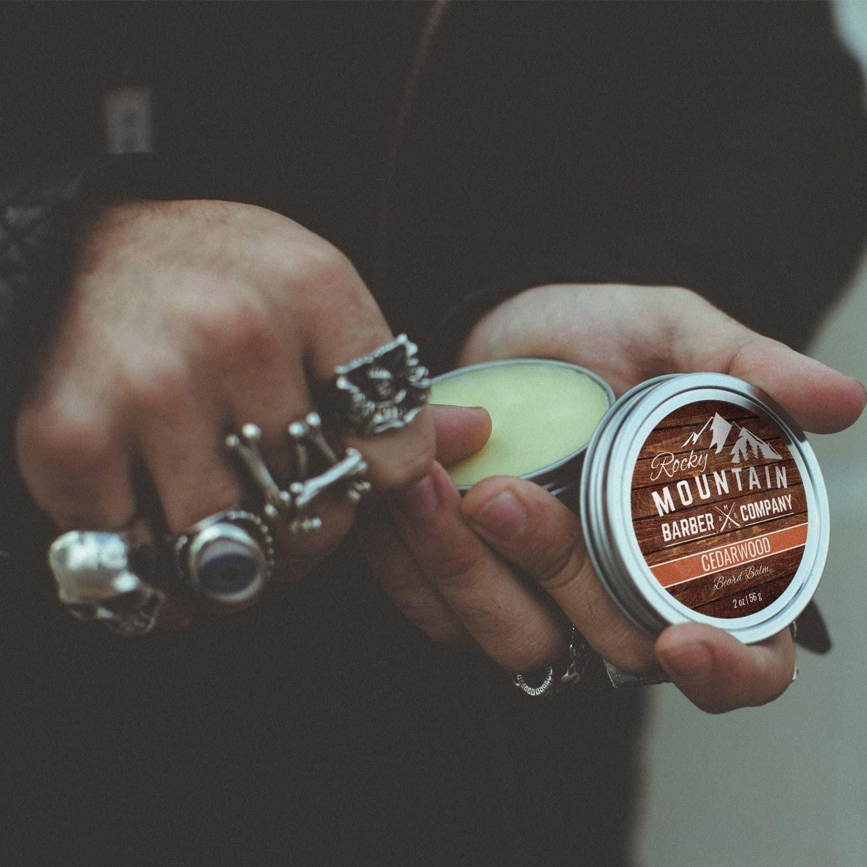 A person holding a metal tin of beard balm