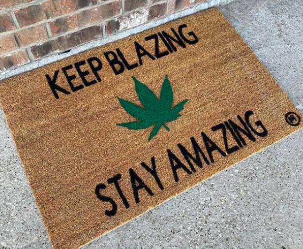 "doormat with a marijuana leaf and a quote that says ""Keep Blazing, Stay Amazing"""
