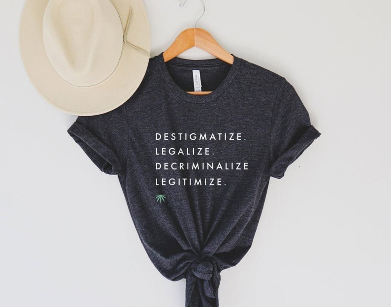 "a t-shirt that says ""destigmatize, legalize, decriminalize, and legitimize"" with a small marijuana leaf below it"