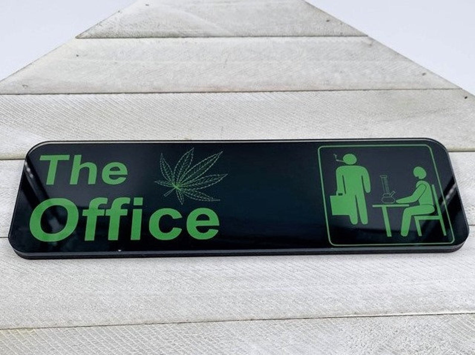 "a black rectangular door sign that says ""The Office"" and has an animated view of a person using a bong and a person smoking a joint"