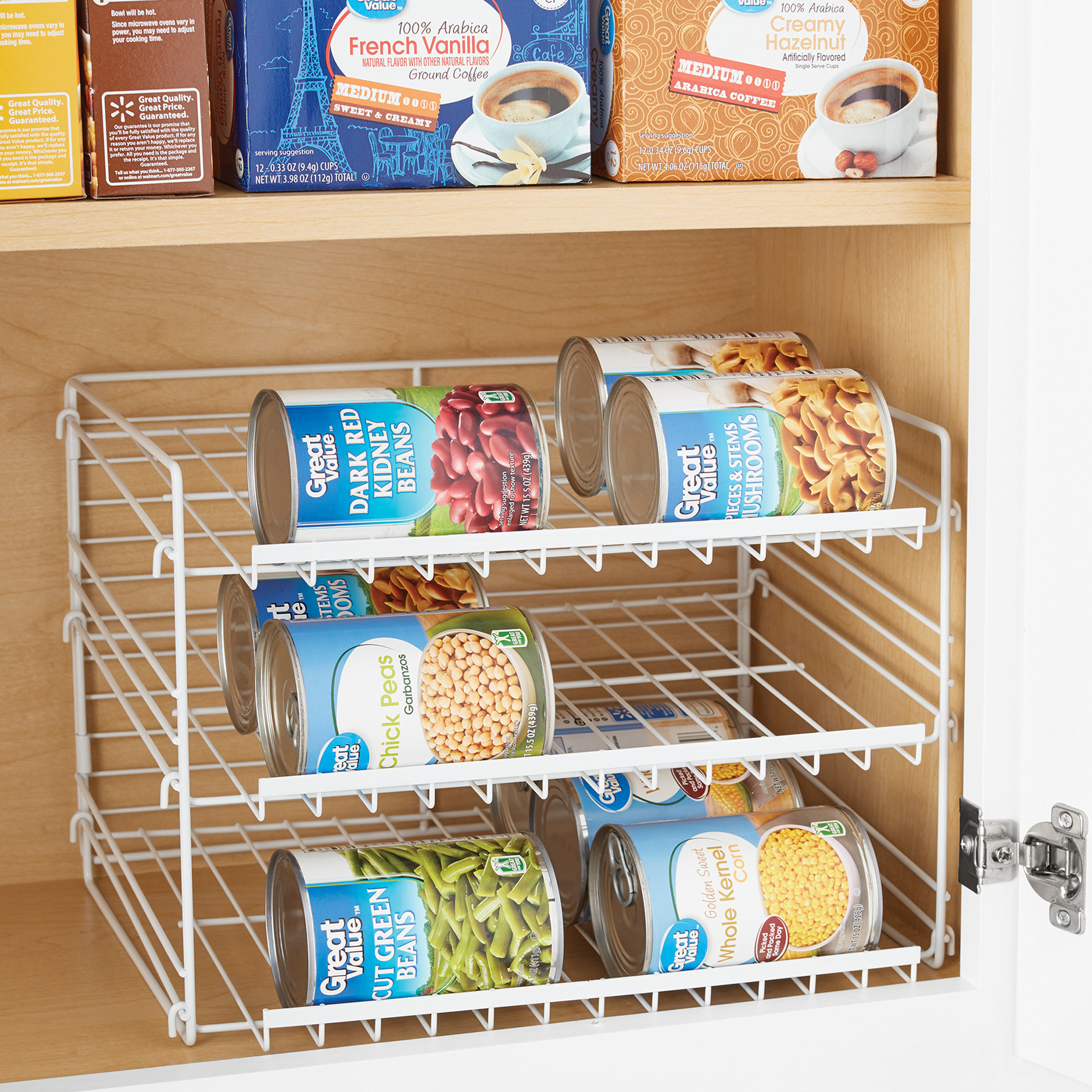 three-tiered white can organizer with cans on the shelves, in a cabinet