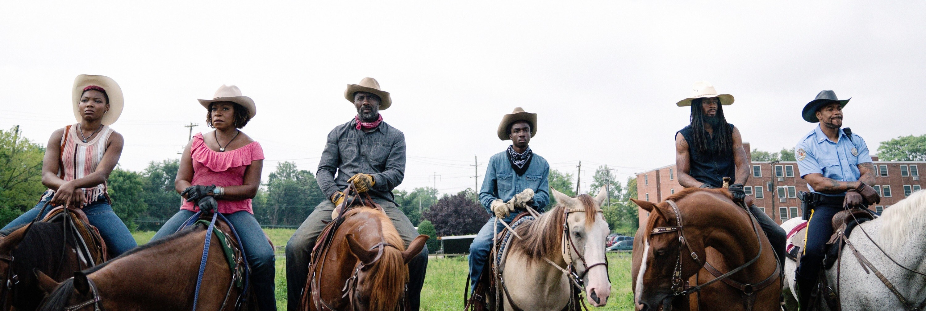 Cowboys and cowgirls sit on their horses side-by-side