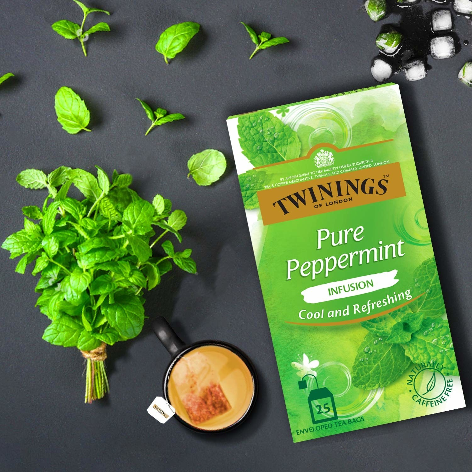 The box of the tea. A cup of peppermint tea and mint leaves are kept next to it.