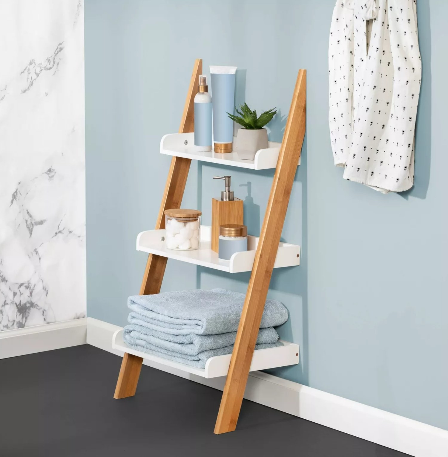 The ladder with bamboo legs and white shelves holding towels and other bathroom necessities