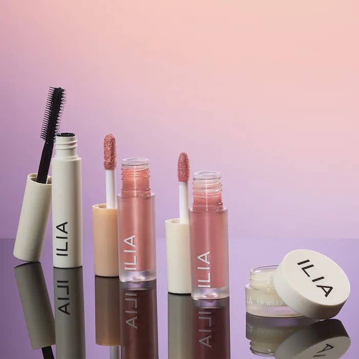 A tube of mascara, lip gloss, eye tint, and a container of lip mask in a row