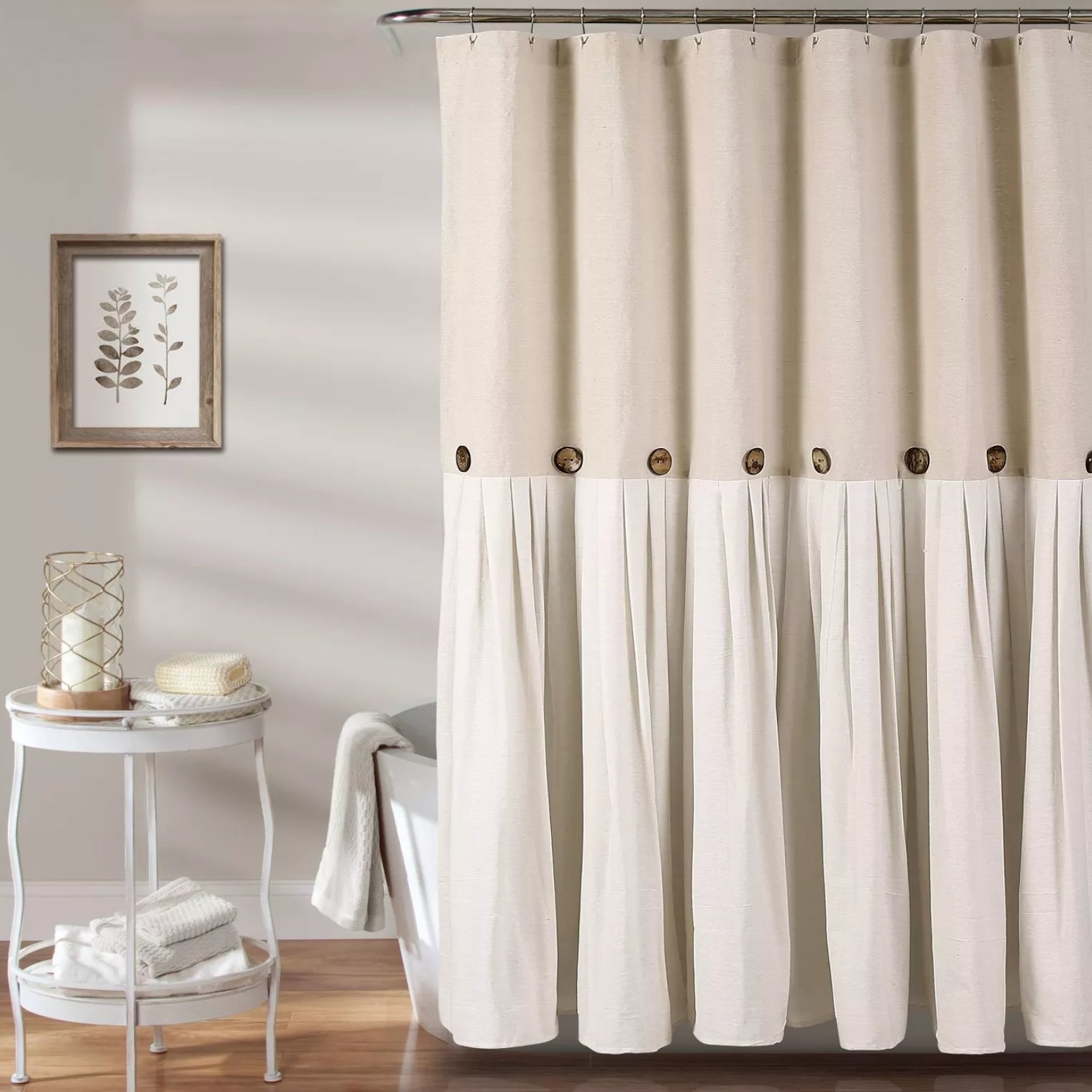 The beige curtain hanging over a bathtub with a side table next to it