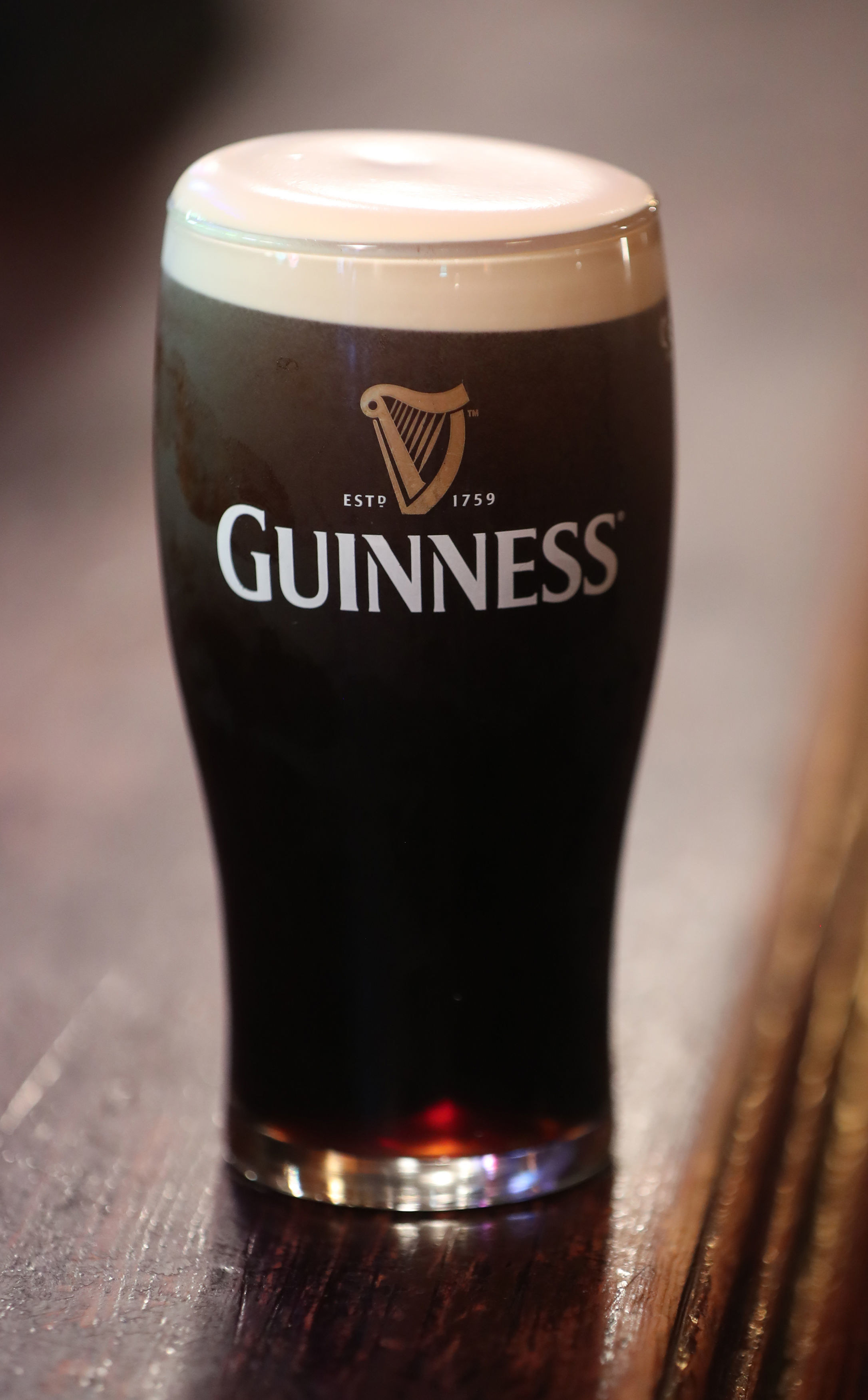 Glass of dark Guinness beer on top of wooden counter