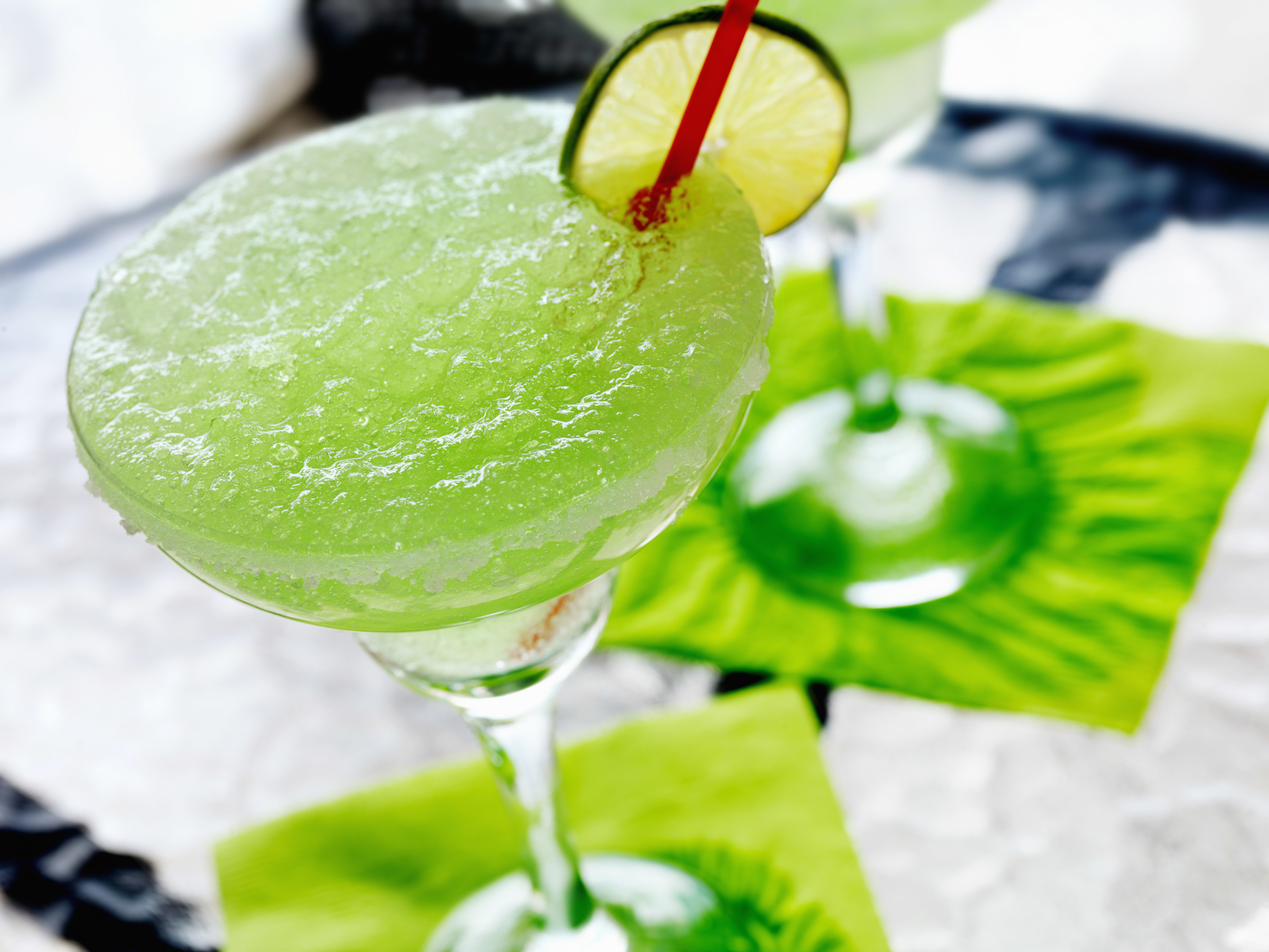 A slushy bright green margarita with a lime wedge and red straw