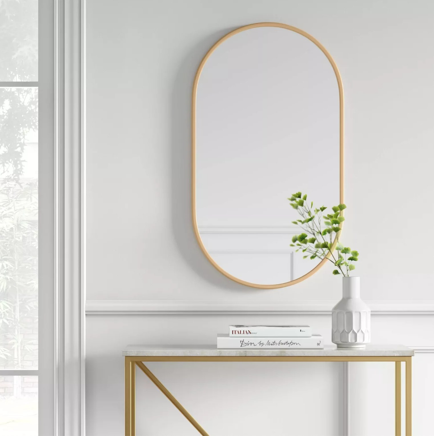 The gold-rimmed mirror hanging above a table with books and a plant
