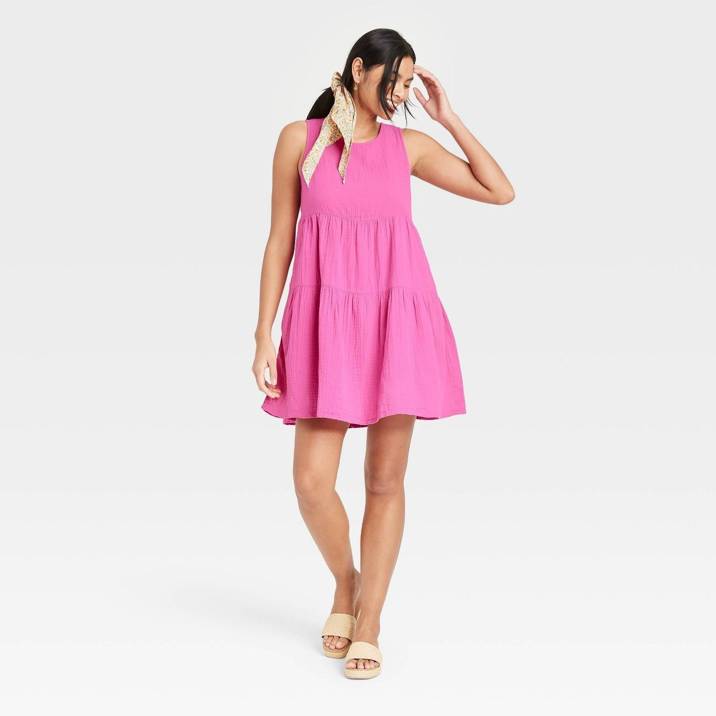 Model wearing pink dress with gauze textured tiers