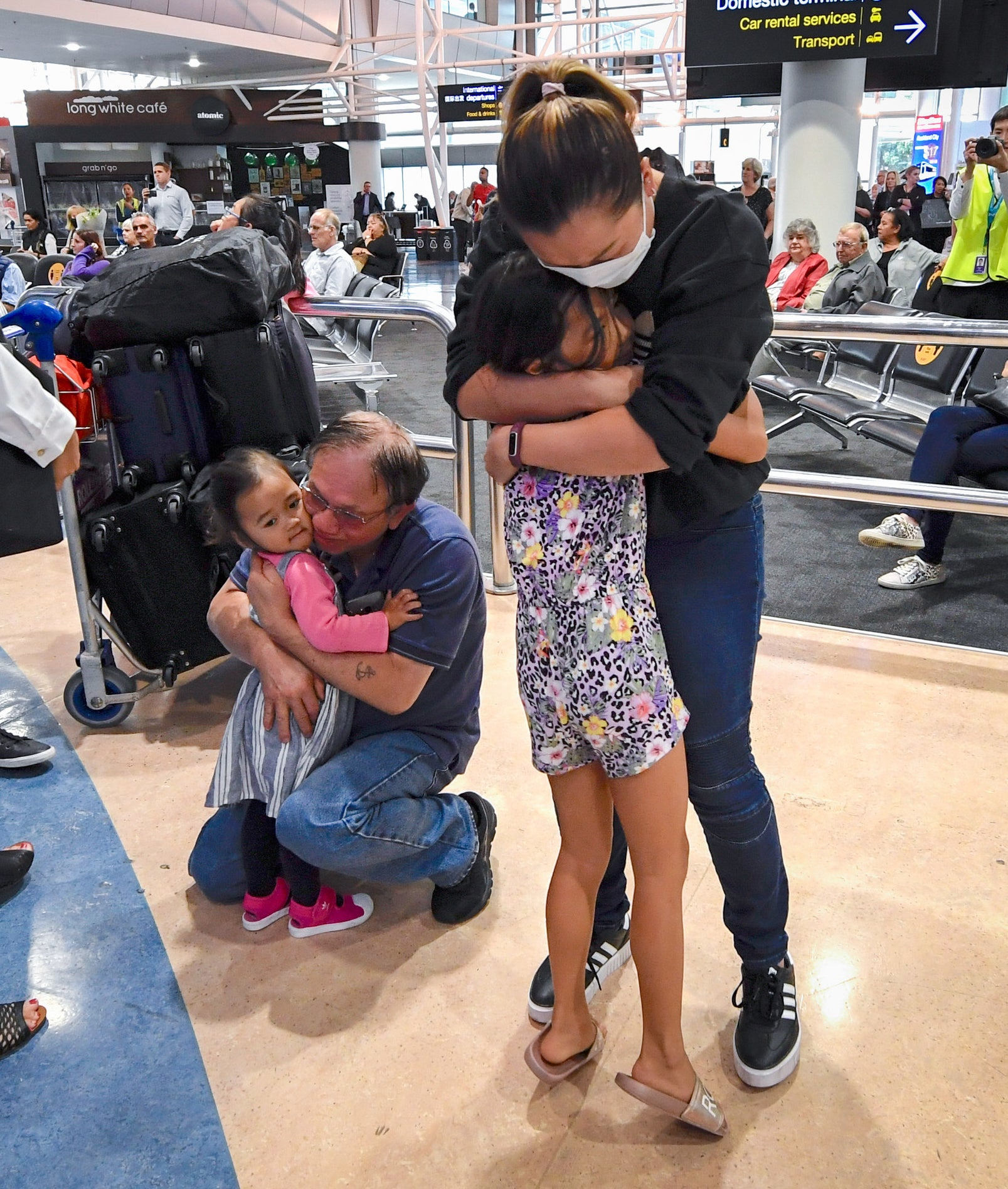Two adults hugging children