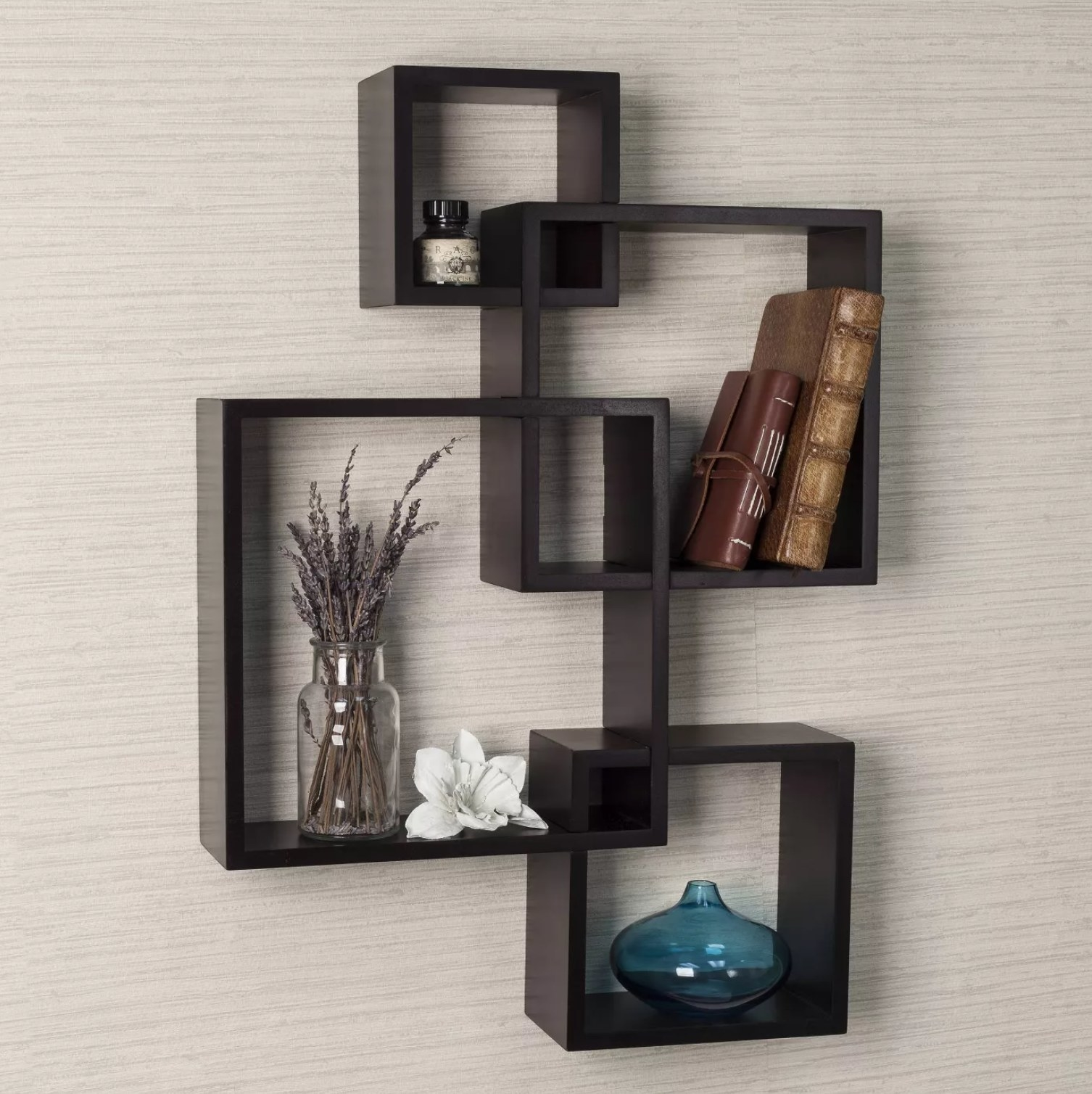 The set of four shelves in dark brown with books and other decorations