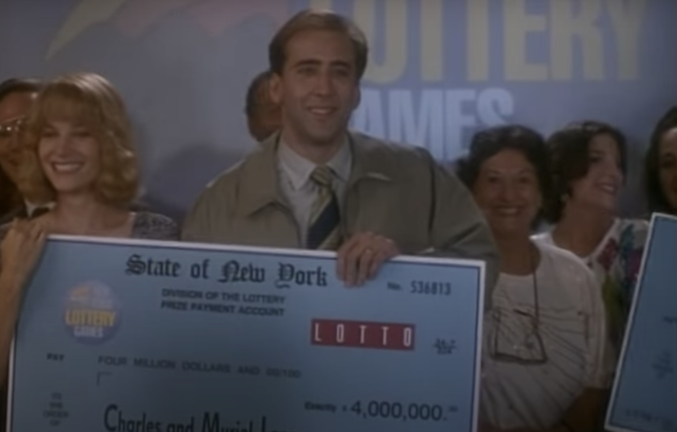 """Nic Cage and Bridget Fonda holding a giant check in """"It Could Happen to You"""""""