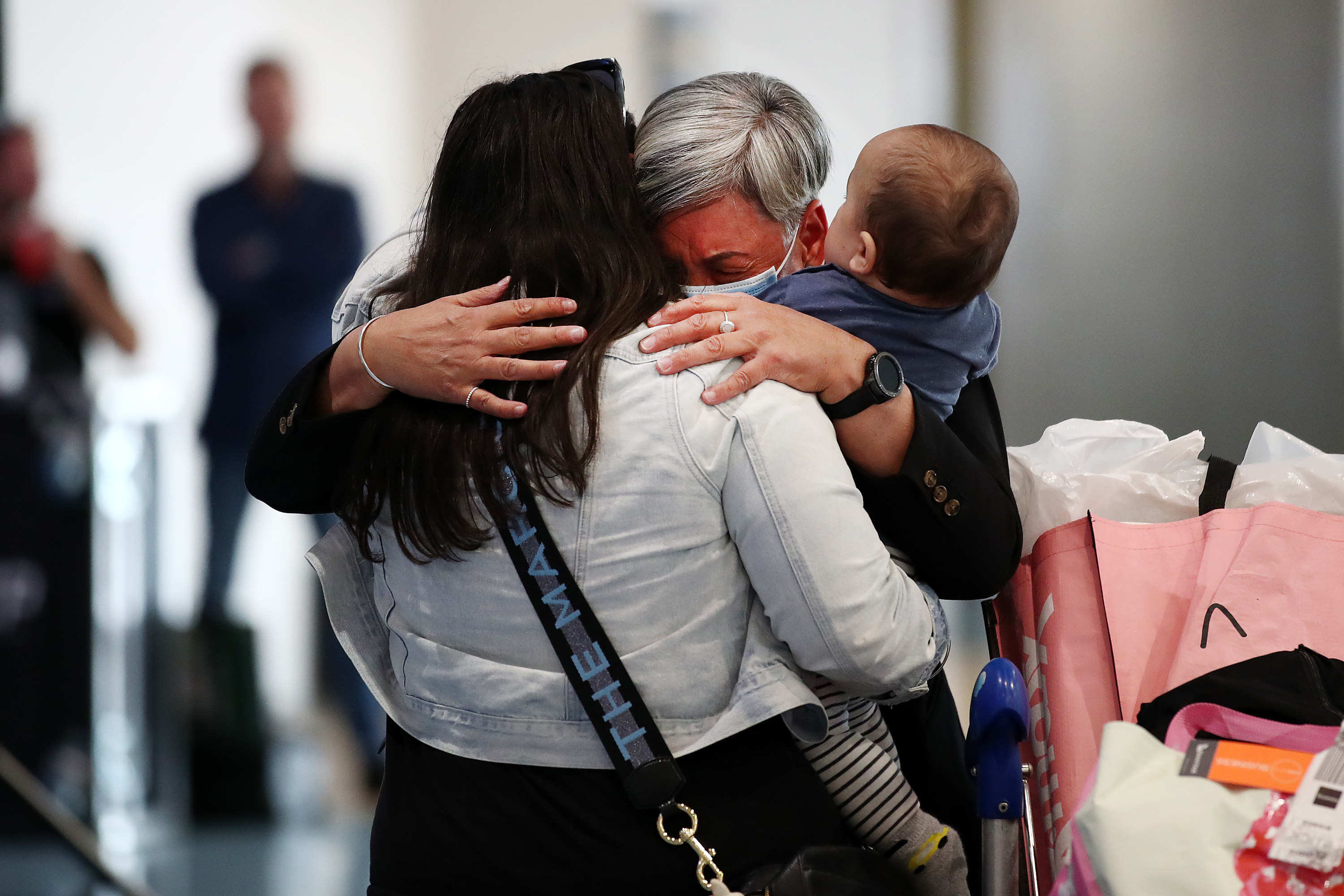 Two adults and a toddler embrace