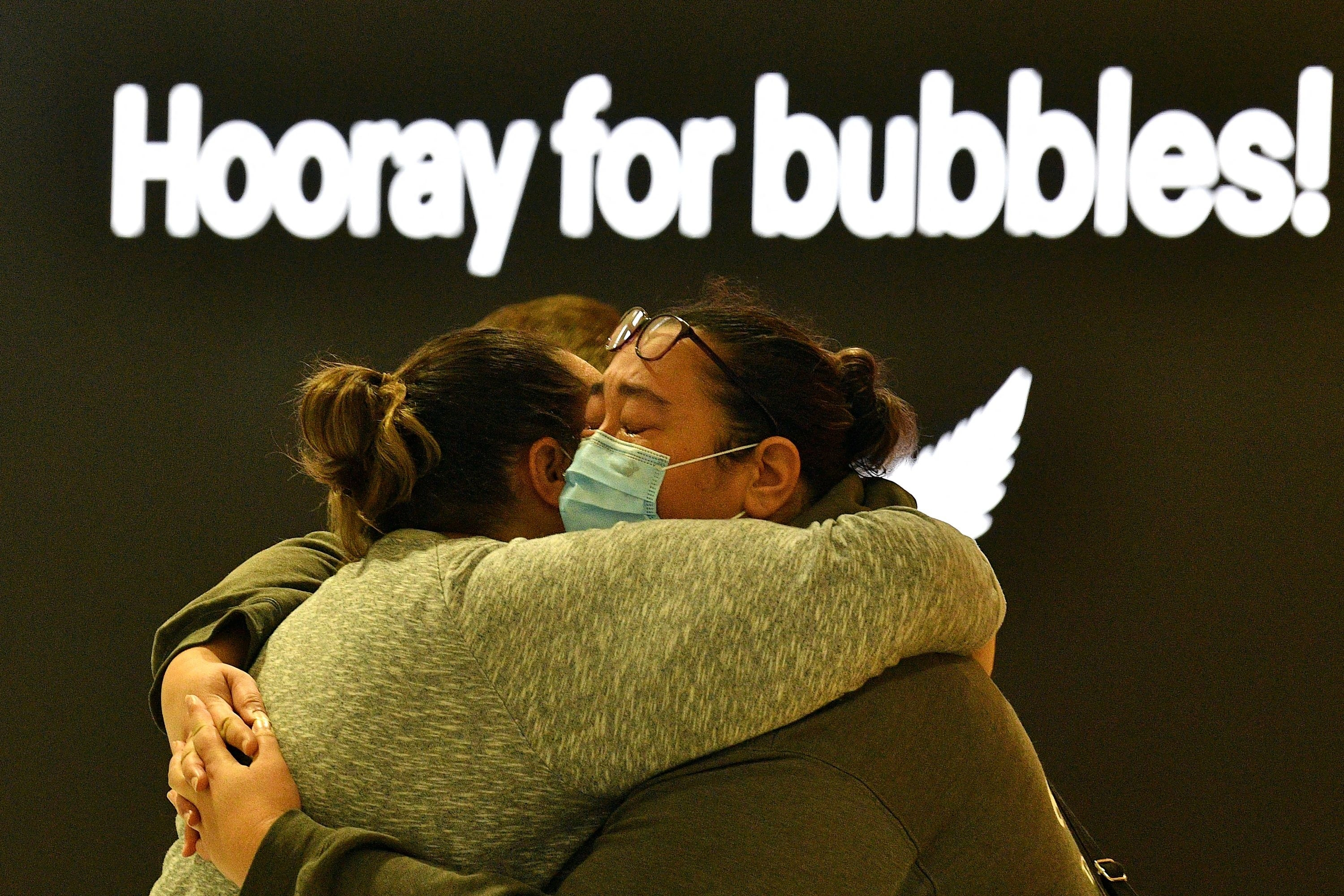 "Two people embrace with a sign that says ""hooray for bubbles!"" above them"