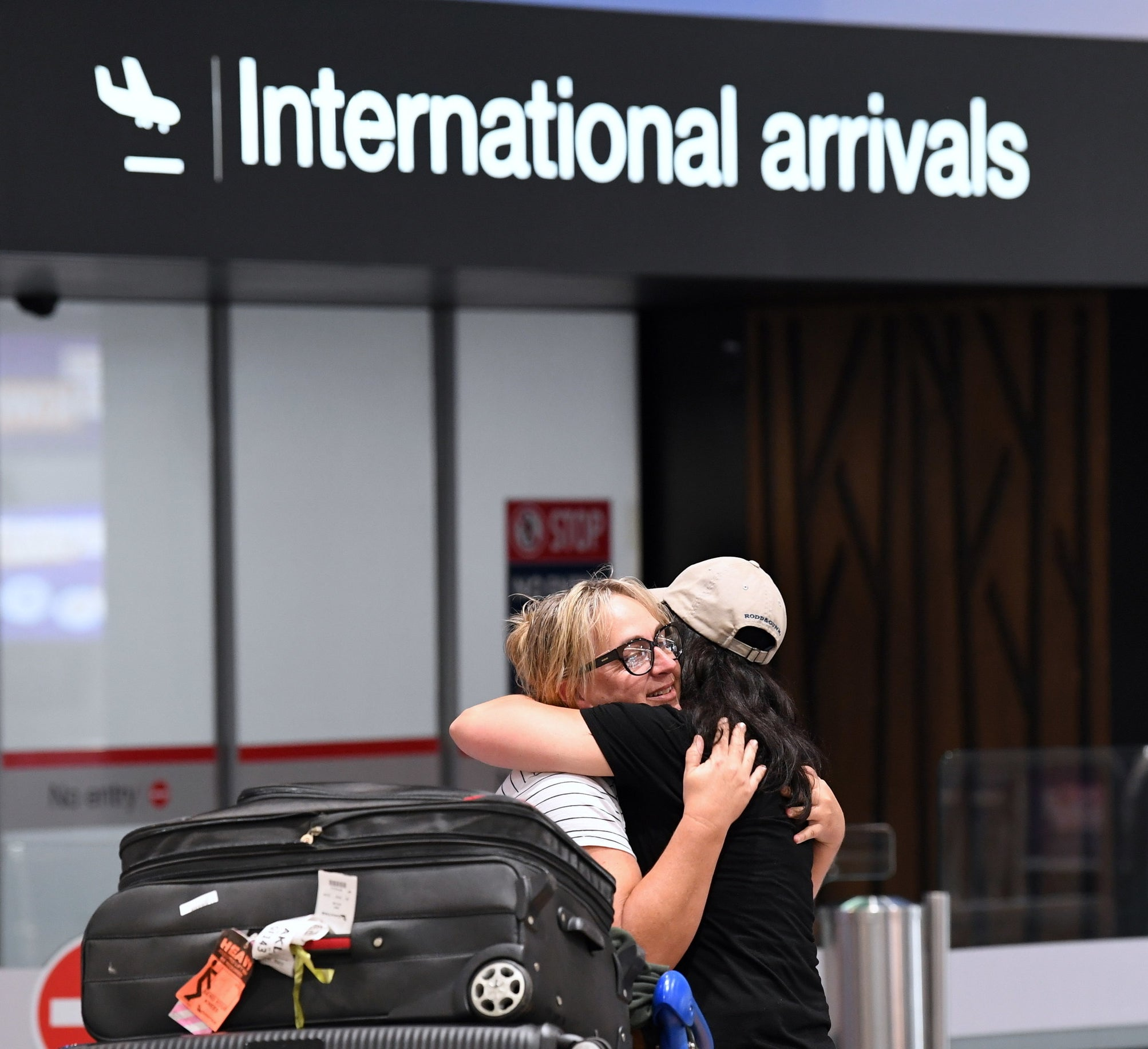 Two people hugging at the arrivals terminal