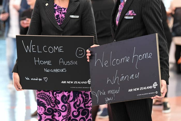 "People holding signs that sat ""Welcome Home Aussie"" and ""Welcome home Whānau"""