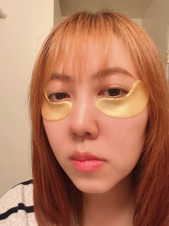 a reviewer wearing the gold eye masks