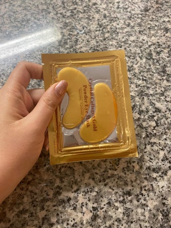 a reviewer holding the individually packaged eye masks