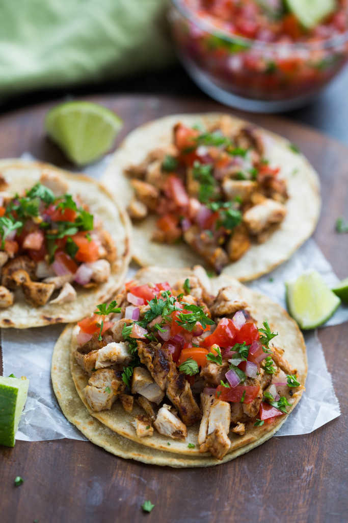 Chicken tacos with tomato and onion.