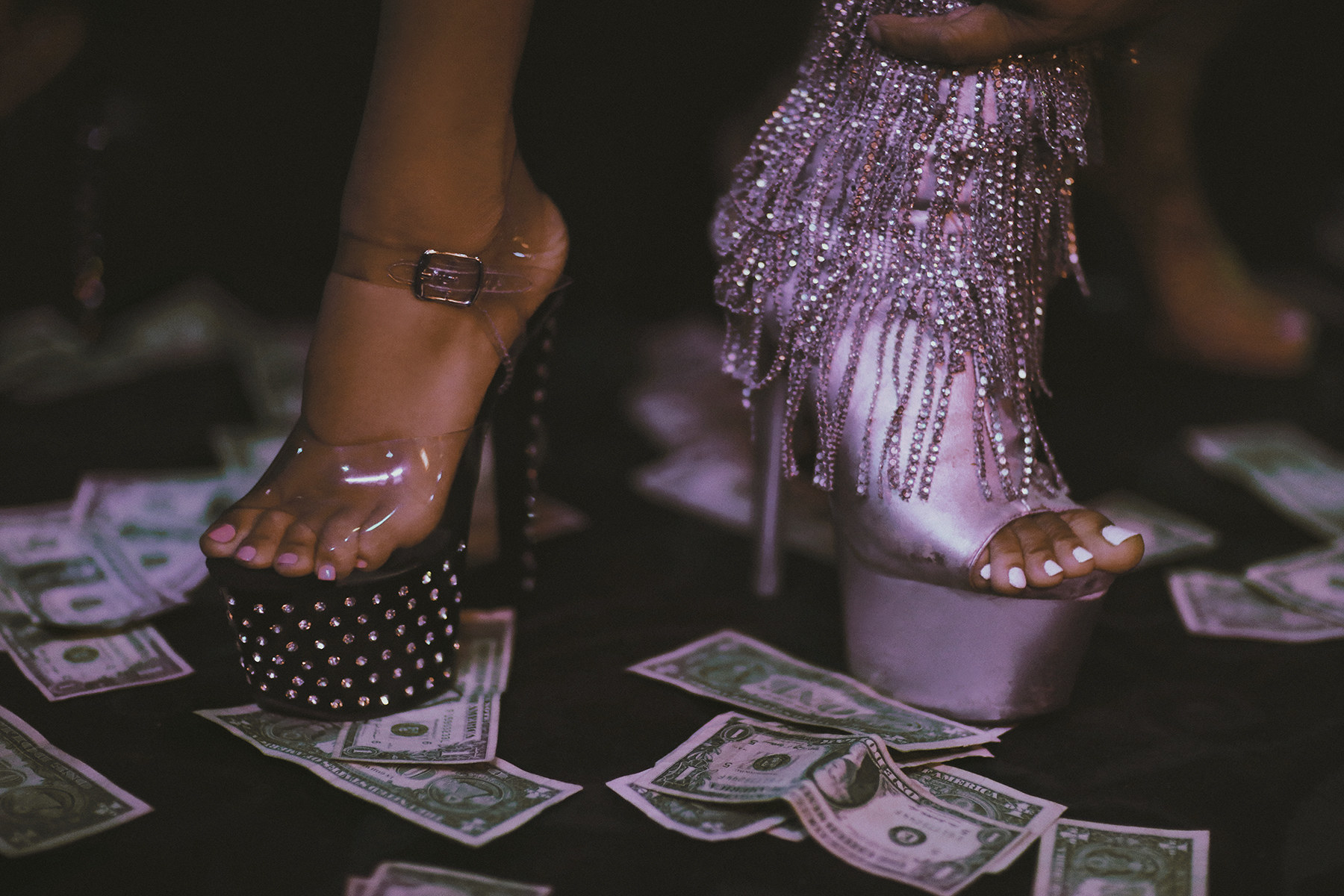 Two women in very high-heeled shoes walking on a floor littered with money