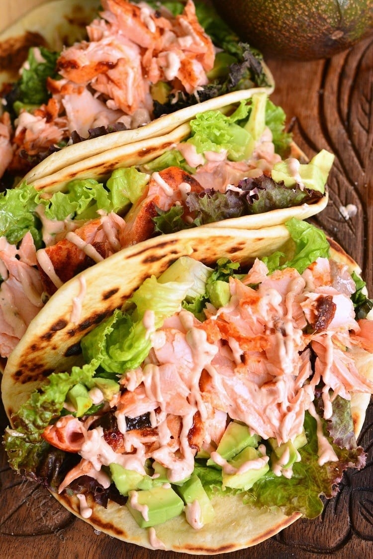 Salmon tacos with avocado, lettuce, and spicy mayo drizzle.