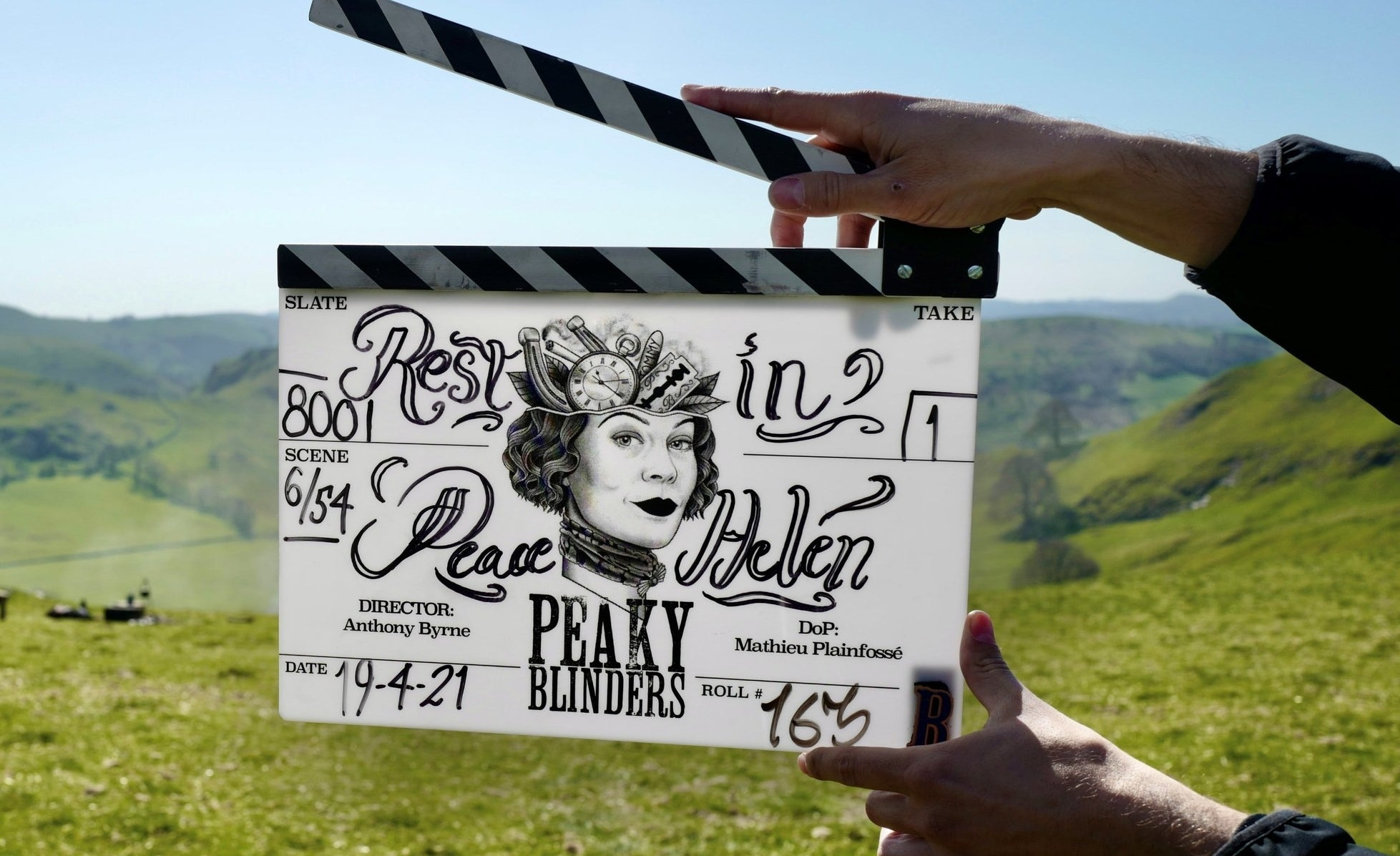 The clapboard features a pocketwatch