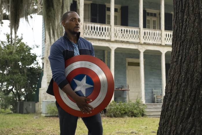 Sam holding the shield in front of a house