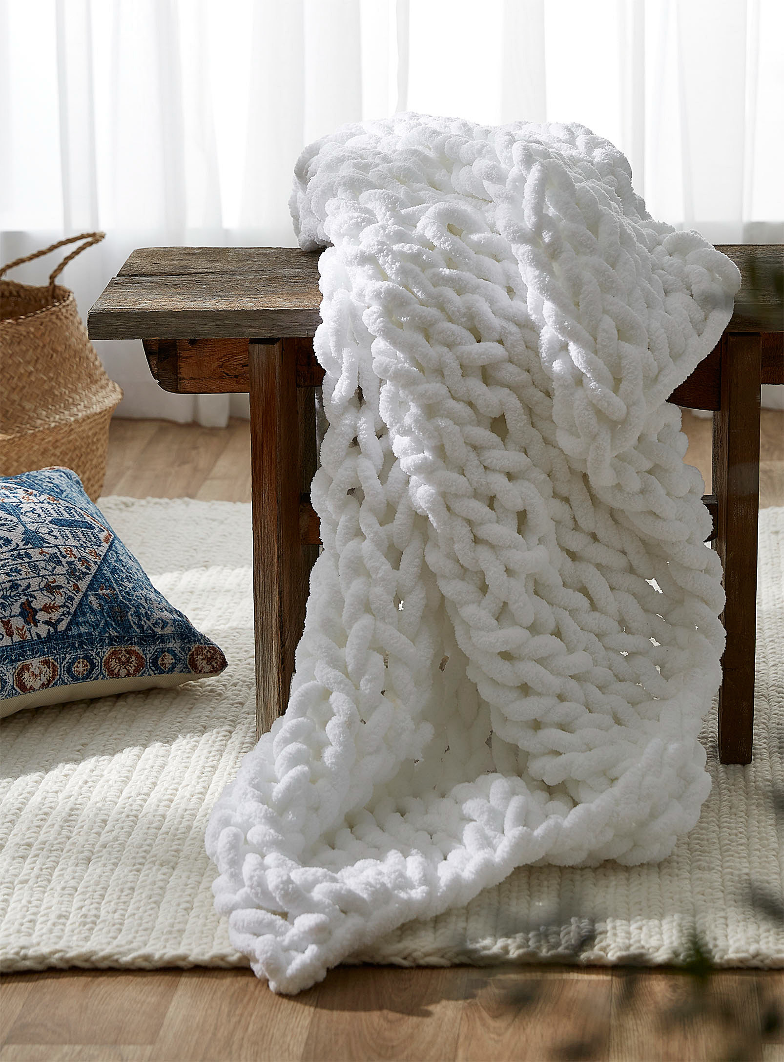 A large throw blanket draped over a bench