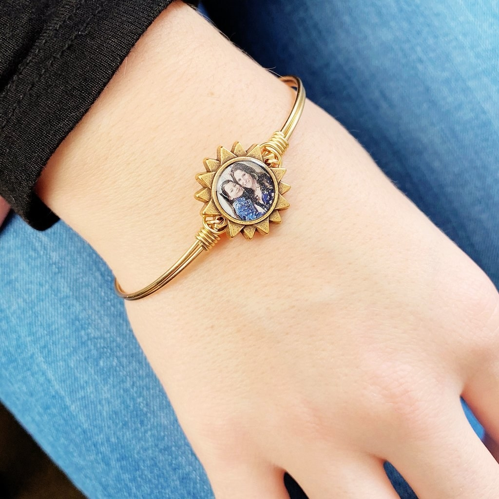 the bangle in gold with a sun in the middle and a picture of an adult and child inside the circle of the sun