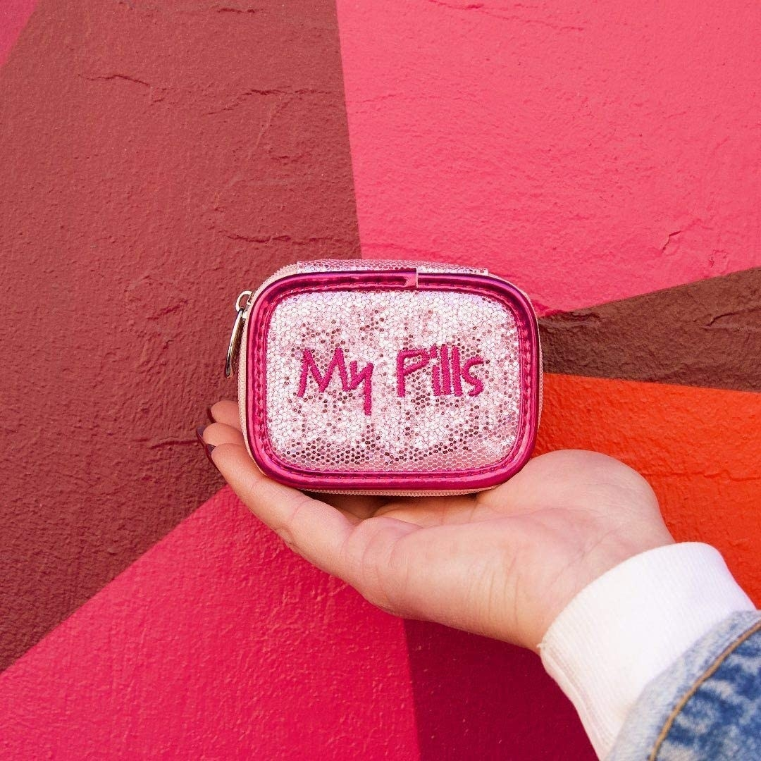 A person holding the pill case in front of a mural